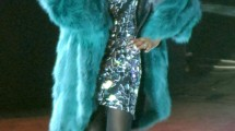 Whitney Houston wearing reversible emerald green fox fur coat.